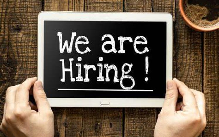 black chalkboard with words WE ARE HIRING! two hands holding the sign